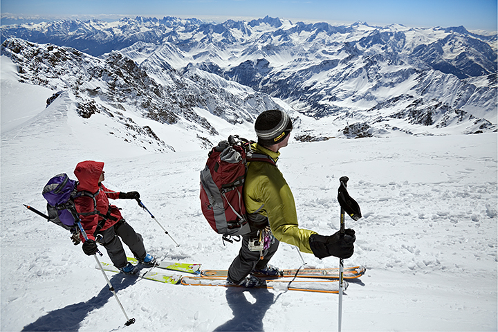 Amy Rasic and Michael Silitch ski touring high in the Alps with the Dolomites behind them in the distance. They are approaching the summit of the Monte San Matteo while on a ski tour of the Ortler area of northern Italy