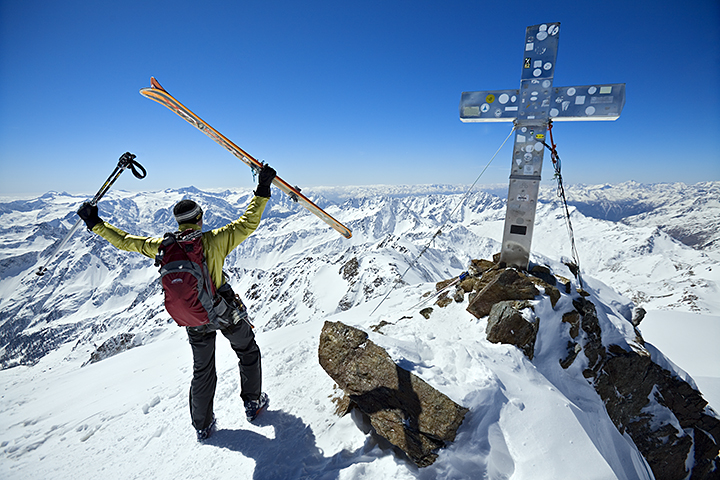 Michael Silitch holding his skis and poles up in celebration of being on the summit of the Monte San Matteo while on a ski tour of the Ortler area of northern Italy